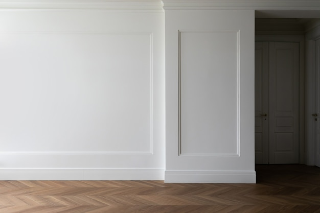 Fragment van klassiek interieur met visgraat parketvloer en wandpanelen met geplaatste lijstwerk en plinten. witte muur met copyspace.