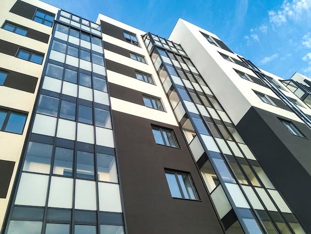 Fragment van modern flatgebouw tegenover blauwe hemel