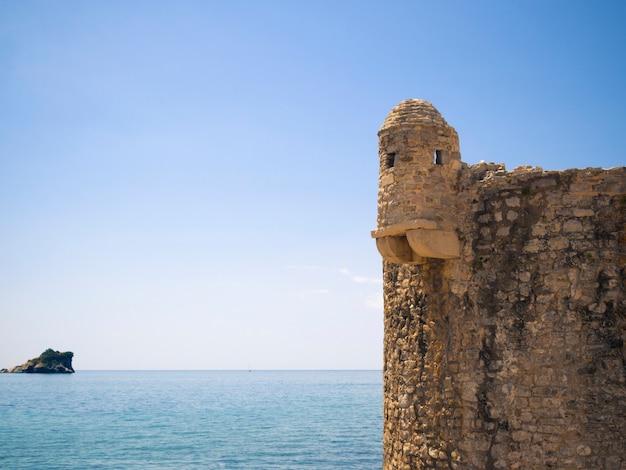 Fragment van oud mediterraan fort met zonnig zeegezicht erachter