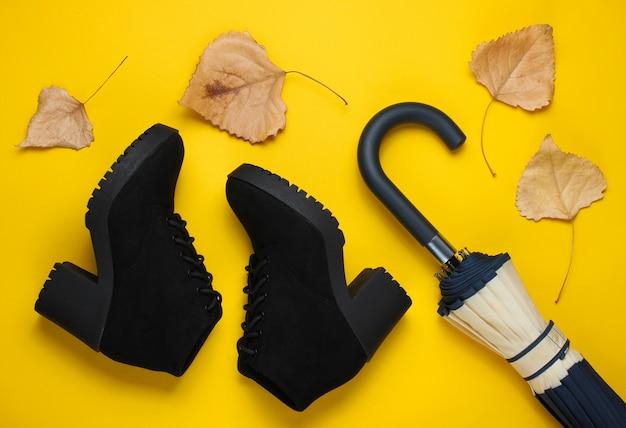 Fragment van parapluhaak, laarzen en gevallen bladeren. bovenaanzicht. herfst accessoires. plat liggen