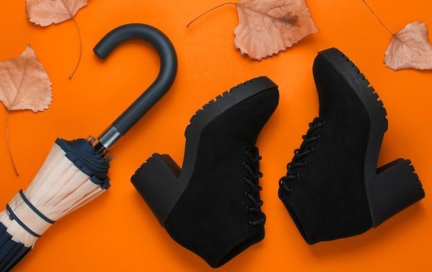 Fragment van parapluhaak, laarzen en gevallen bladeren op oranje achtergrond. bovenaanzicht. herfst accessoires. plat leggen