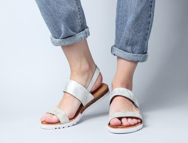 Fragment van vrouwelijke benen in spijkerbroek en trendy lederen sandalen op wit. stijlvolle zomerschoenen voor dames.