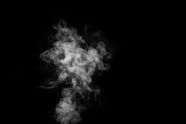 Fragment van witte hete krullende stoomrook geïsoleerd op een zwarte achtergrond, close-up. maak mystieke halloween-foto's. abstracte achtergrond, ontwerpelement