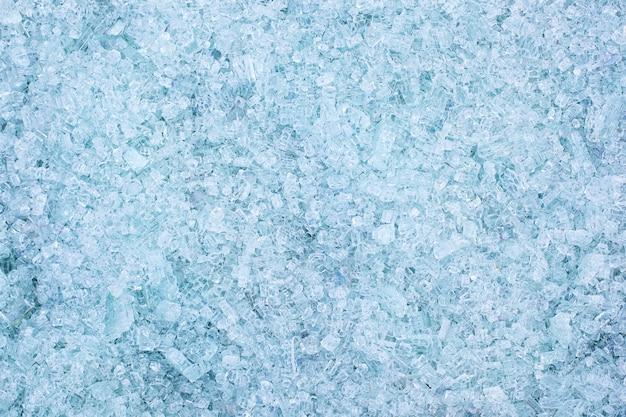 Fragmenten van blauw glas. kleine en scherpe fragmenten van gebroken glas. scherven voor het maken van nieuw glas zijn klaar om opnieuw te worden gesmolten. veel deeltjes gebroken glas. recycling van afval. ecologie, afval