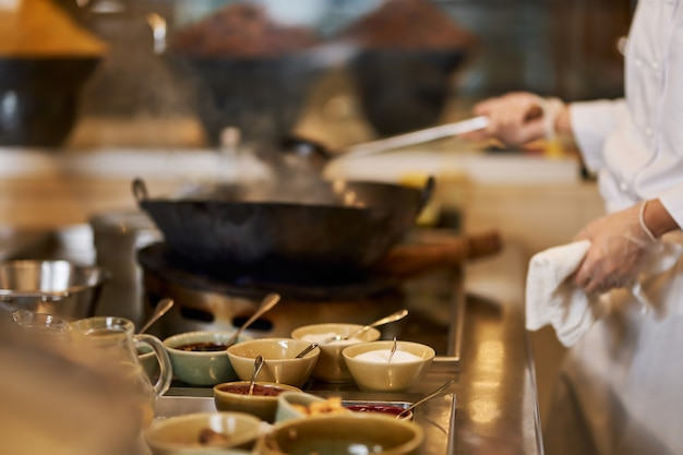 Fragmentfoto van chef-kok die meer ingrediënten in wok doet