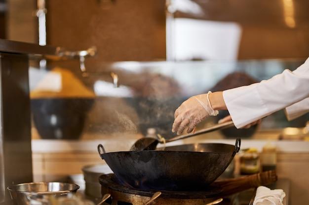 Fragmentfoto van heerlijk gerecht dat in een wok wordt bereid
