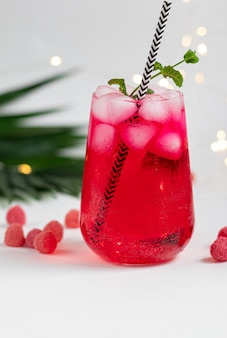 Framboos-berberisdrank in een transparant glas met ijs. palmtakken en frambozen toegevoegd. witte achtergrond.