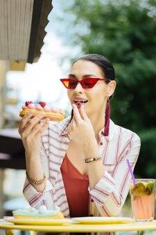 Framboos. emotionele bezoeker van een café dat lacht en naar het heerlijke dessert kijkt terwijl hij een framboos eet