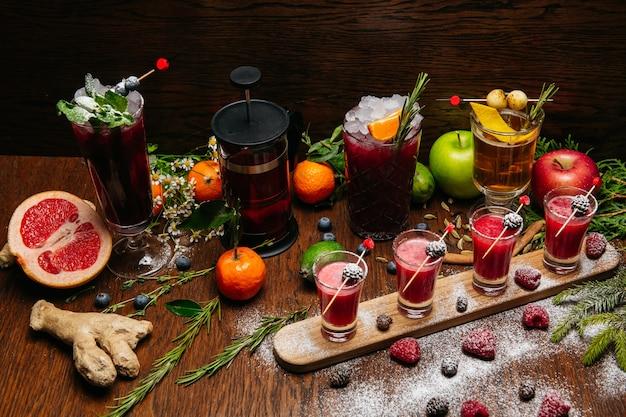 Framboos shot cocktails met dennenappels met citruscocktails op het houten bureau op de tafel in het restaurant