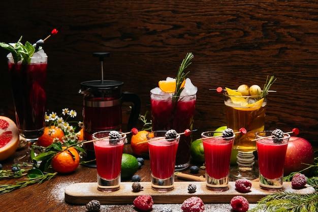 Framboos shot cocktails met dennenappels met fruitcocktails op het houten bureau op de tafel in het restaurant