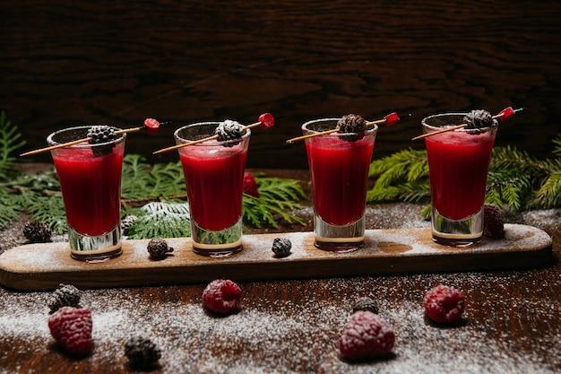 Framboos shot cocktails met dennenappels op het houten bureau op de tafel in het restaurant