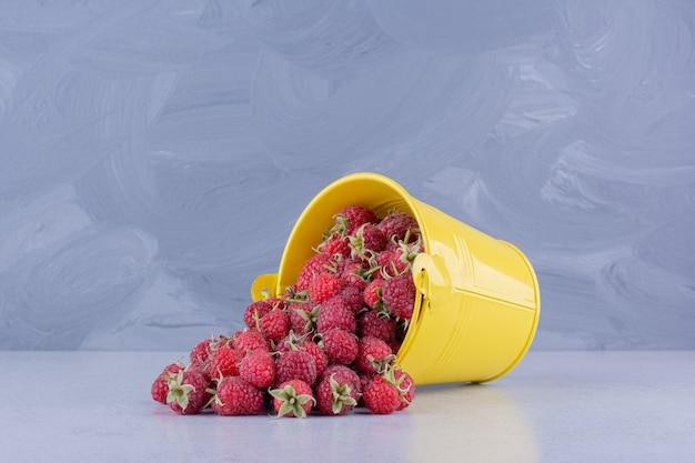 Frambozen die uit een gele emmer op marmeren achtergrond gieten. hoge kwaliteit foto