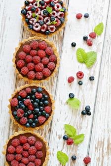 Frambozen- en bosbessentaartjes met chocoladeganache, verse bessen en muntblaadjes, selectieve aandacht.
