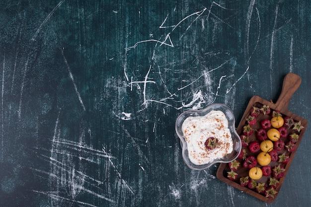 Frambozen en kersen in een houten schotel met een glas ijs