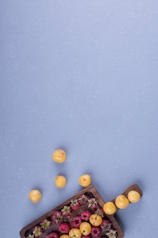 Frambozen en kersen in een houten schotel