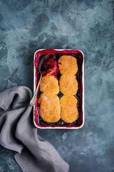 Frambozen en zwarte bessen schoenmaker met frambozenroomijs in ovenschaal. zelfgemaakte fruittaart gebak. grijze vintage achtergrond. bovenaanzicht.