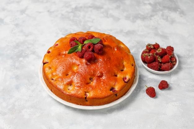 Frambozencake met poedersuiker en verse frambozen op een licht. zomer berry dessert.