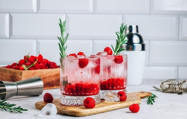 Frambozenlimonade in een glas met ijs en verse rozemarijn op een stenen ondergrond. selectieve focus