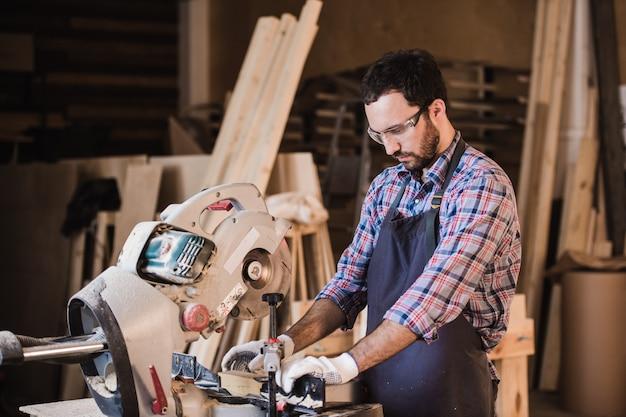 Frame-aannemer met behulp van een cirkelzaag om de lengte van houten stijlen af te knippen.
