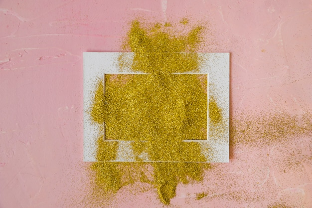 Frame bedekt met gele pailletten op roze tafel
