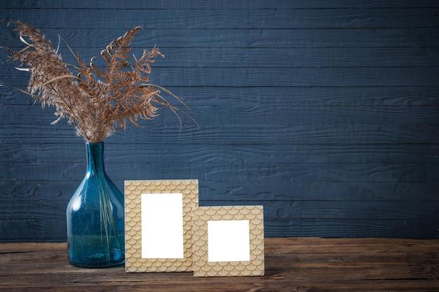 Frame en gedroogde bloemen in blauwe glazen vaas op oude houten tafel