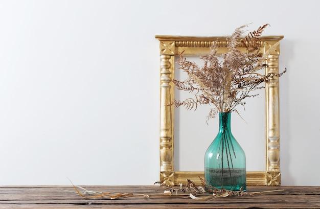 Frame en gedroogde bloemen in groene vaas op oude houten plank
