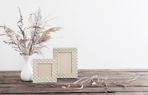 Frame en gedroogde bloemen in witte vaas op oude houten plank