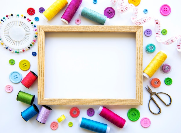 Frame en naai-accessoires en stof op een wit oppervlak. naaigaren, naalden, spelden, stof, knopen en naai-centimeter. bovenaanzicht, plat gelegd.