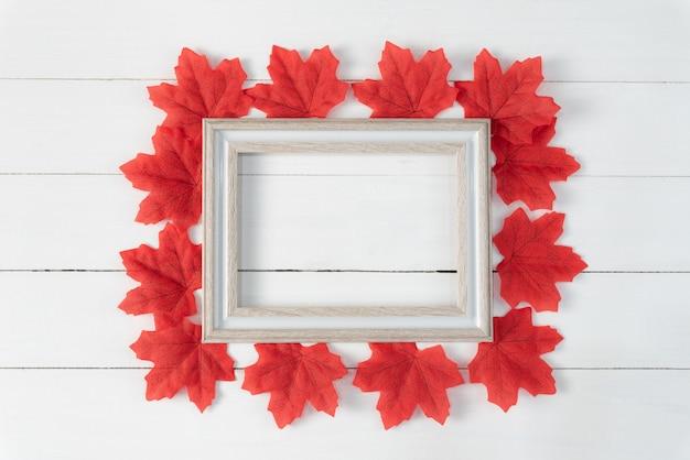 Frame en rode esdoornbladeren op witte houten achtergrond