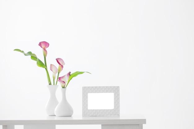 Frame en roze calla lelie in vaas op witte achtergrond