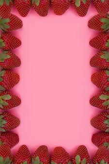 Frame gemaakt van aardbeien op roze achtergrond