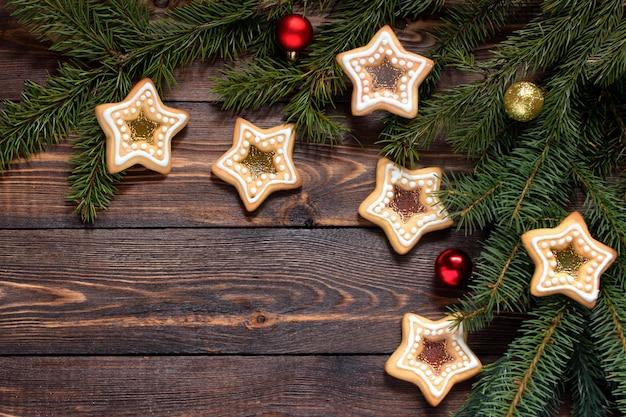 Frame gemaakt van dennentakken en zelfgemaakte koekjes en kerstspeelgoed op een houten bruine ondergrond