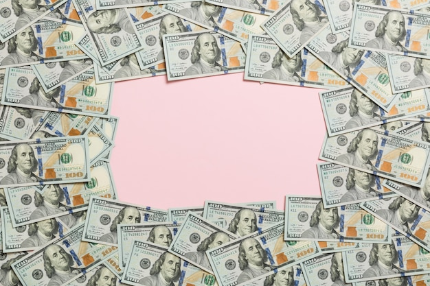 Frame gemaakt van dollars met copyspace in het midden. bovenaanzicht van het bedrijfsleven op roze achtergrond met kopie ruimte