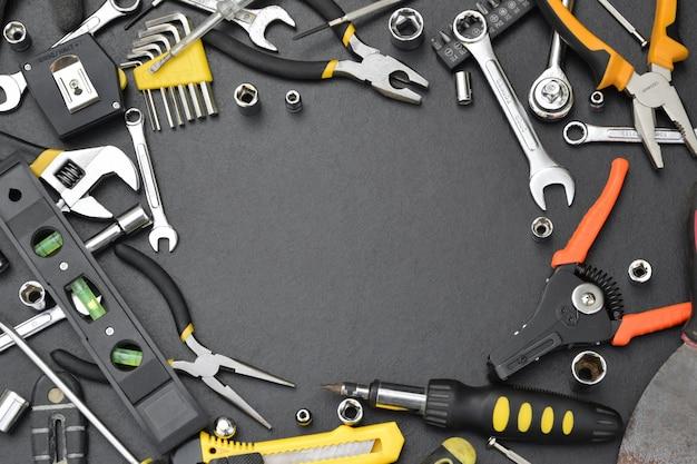 Frame gemaakt van handyman toolkit op zwarte houten tafel, bovenaanzicht