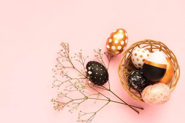 Frame gemaakt van houten beschilderde eieren in goud, zwart en roze kleuren op roze achtergrond. gelukkige pasen-achtergrond met exemplaarruimte