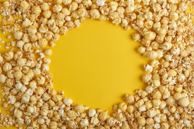 Frame gemaakt van karamel popcorn op gele achtergrond kopie sapce bovenaanzicht