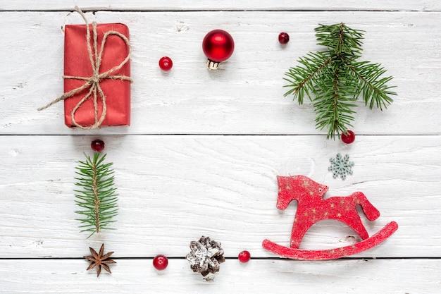 Frame gemaakt van kerstcadeau, dennenappels, dennentakken, rode bal, bessen en speelgoedpaard