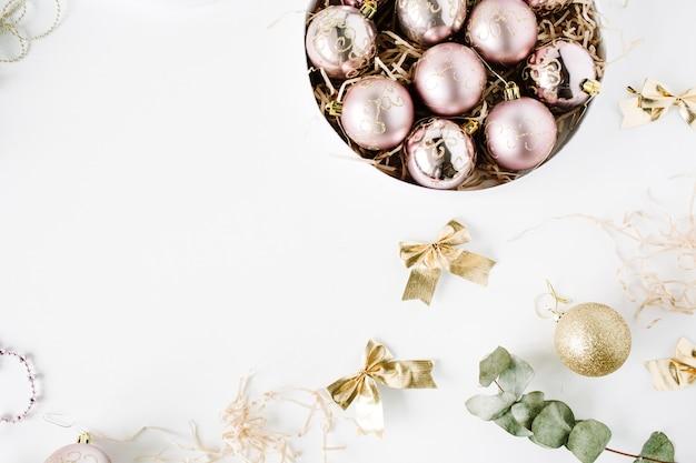 Frame gemaakt van kerstversiering met glazen kerstballen, klatergoud, strik, eucalyptus.