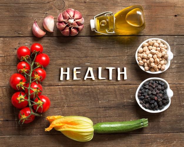 Frame gemaakt van kikkererwten in kommen met groenten en tekst gezondheid op een houten tafelblad bekijken