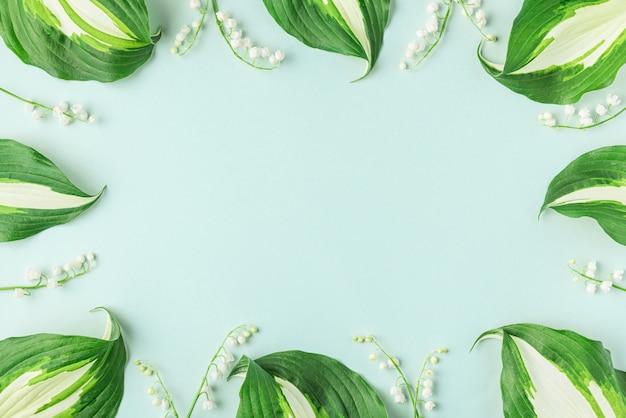 Frame gemaakt van lente lelietje-van-dalen bloemen op pastelblauw oppervlak