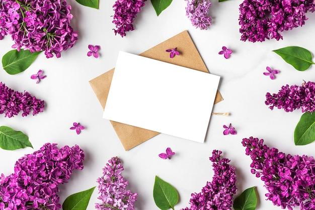Frame gemaakt van lente lila bloeiende bloemen met lege wenskaart op witte ondergrond white
