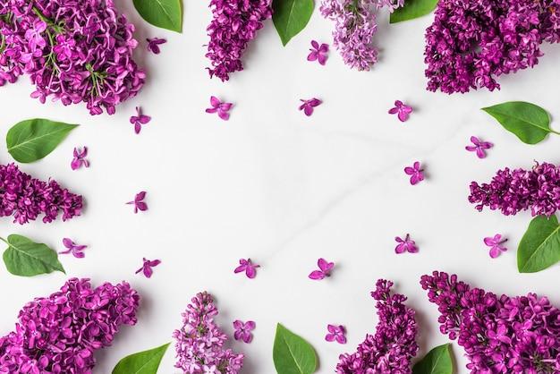 Frame gemaakt van lentelila bloemen op pastelblauw oppervlak