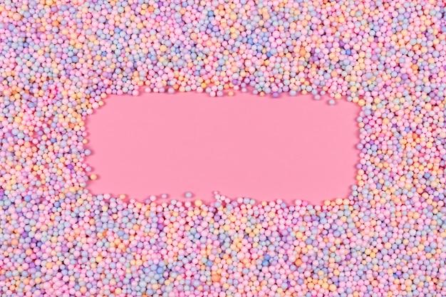 Frame gemaakt van pastelkleurige ballen op roze piepschuim of piepschuim