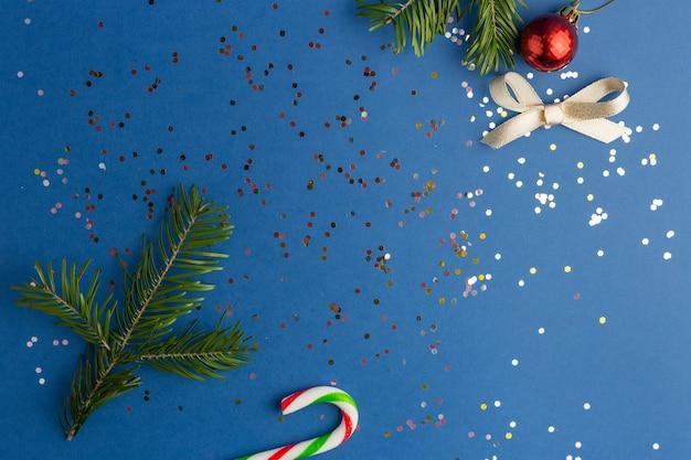 Frame gemaakt van pijnboomtakken. blue christmas achtergrond met veelkleurige confetti. platliggende stijl. kleur van het jaar.