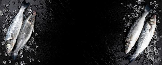 Frame gemaakt van rauwe zeebaars vis op zwart, bovenaanzicht