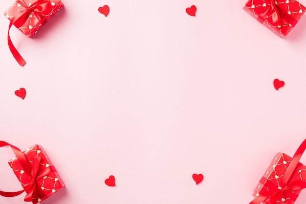 Frame gemaakt van rode geschenkdoos met strik en hout rode harten vormige compositie wenskaart