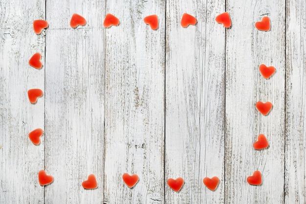 Frame gemaakt van rode hartvormige snoepjes op witte houten achtergrond voor valentijn