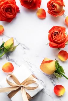 Frame gemaakt van rode rozen en bloemblaadjes met geschenkdoos op marmeren achtergrond