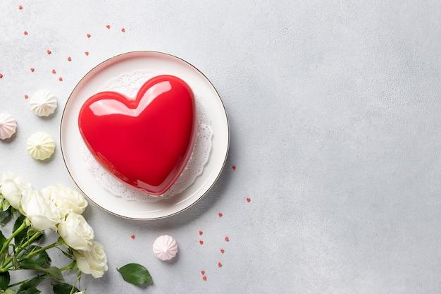 Frame gemaakt van roze bloemen, hartvorm mousse cake en snoep