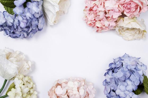 Frame gemaakt van roze en beige rozen, blauwe hortensia op witte achtergrond.